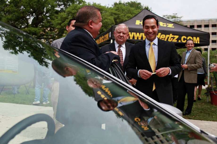 Mario Rocha, area manager for Hertz at the San Antonio International Airport (left) talks with Mayor Julián Castro, joined by Bill Barker with the Office of Environmental Policy (center) and Castro adviser Adam Greenup (far left). Photo: Lisa Krantz, San Antonio Express-News / SAN ANTONIO EXPRESS-NEWS