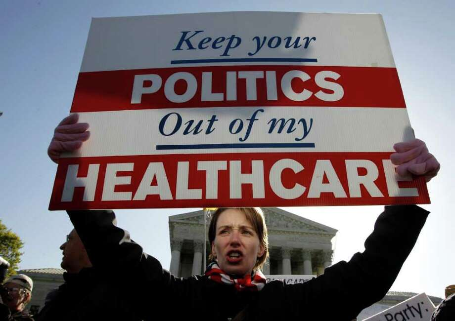 Amy Brighton from Medina, Ohio, rallied in front of the Supreme Court in Washington this week as the justices heard arguments on the health care law. Photo: Charles Dharapak, Associated Press