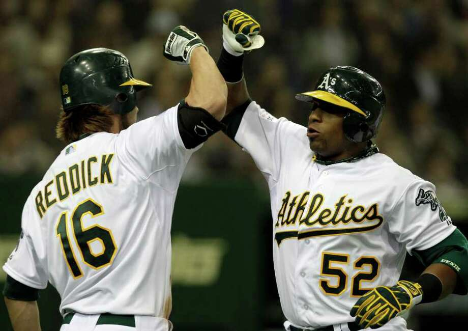 Oakland's Yoenis Cespedes (right) celebrates with teammate Josh Reddick after hitting a two-run shot. Photo: AP