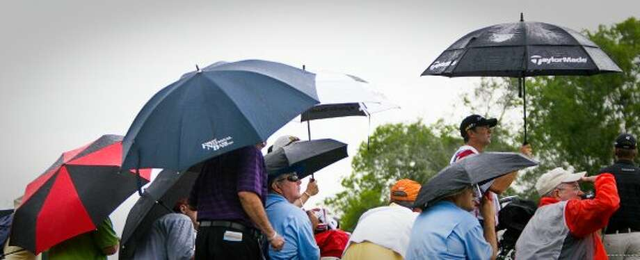 Louis Loyd, of Bay City, center,and other golf fans find shelter from the rain by using umbrellas at the 16th hole. (Nick de la Torre / Houston Chronicle)