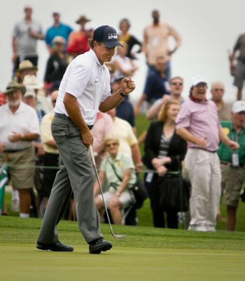 Phil Mickelson pumps his fist after making a long put at the first hole. (Nick de la Torre / Houston Chronicle)