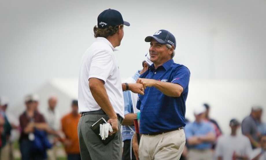 Fred Couples, facing, bumps fists with Phil Mickelson after they both made long putts at the first hole. (Nick de la Torre / Houston Chronicle)