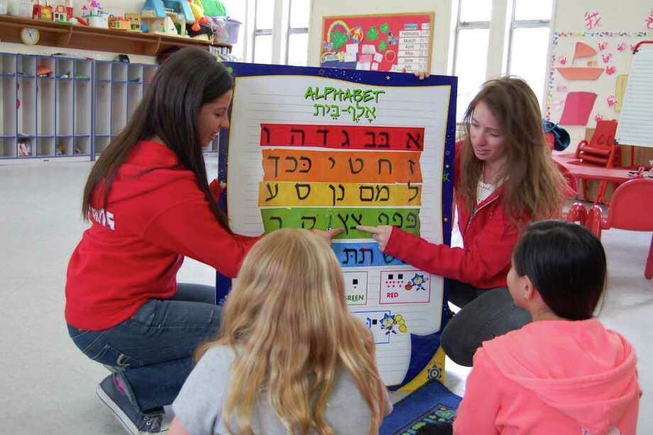 Jordana Adler and Gabi Salomon of Hebrew Wizards teach fellow students letters of the Hebrew alphabet on Thursday, March 29, 2012. Ten teens from Hebrew Wizards will travel to Atlanta this week to share their program with a Hebrew school there. Photo: Contributed Photo
