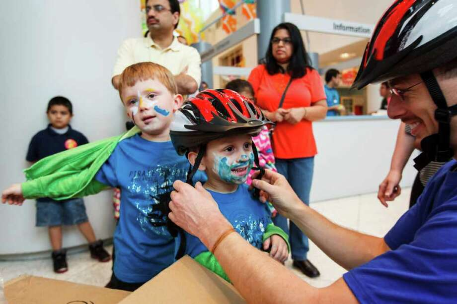 Noel Rodrigues, 3, has a new helmet fitted to his head by Mark Knight as his older brother Nikolas Rodrigues looks on during the Texas Medical Association's Hard Hats for Little Heads project, giving away 75 free bicycle helmets by Baylor College of Medicine students at the Children's Museum of Houston, Thursday, March 29, 2012, in Houston. Photo: Michael Paulsen, Houston Chronicle / © 2012 Houston Chronicle