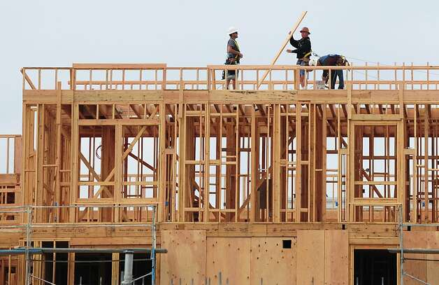 Construction workers are seen atop a builing of new apartments for sale in Alhambra, east of downtown Los Angeles on March 23, 2012 in California. Sales of new homes in the United States slipped for the second straight month in February but the median price of homes sold picked up sharply, according to the Commerce Department. AFP PHOTO/Frederic J. BROWN (Photo credit should read FREDERIC J. BROWN/AFP/Getty Images) Photo: Frederic J. Brown, AFP/Getty Images
