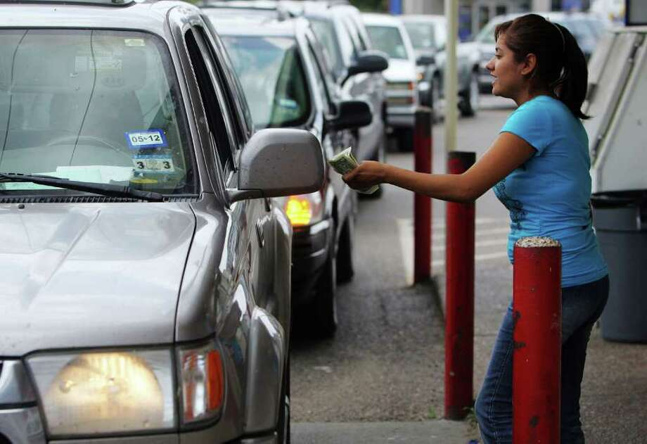 Angela Rodriguez collects money for Mega Millions tickets from a steady stream of Town and Country customers in McAllen on Thursday Photo: Gabe Hernandez / The Monitor