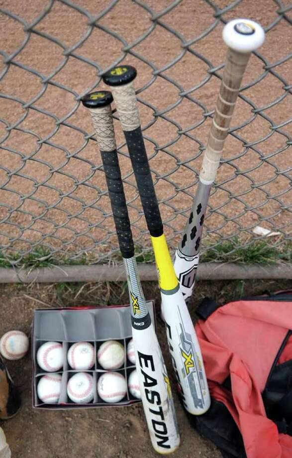 New BBCOR bats which are made from a composite but simulate wood lean against the fence at Greenwich High School's baseball diamond before Thursday's scrimmage against Westhill on March 29, 2012. Photo: Lindsay Niegelberg / Stamford Advocate