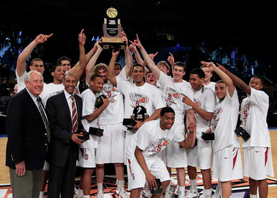 Stanford coach Johnny Dawkins (second from front left) and Aaron Bright (second from front right), who won most outstanding player honors, pose with teammates after capturing the NIT title. Photo: AP