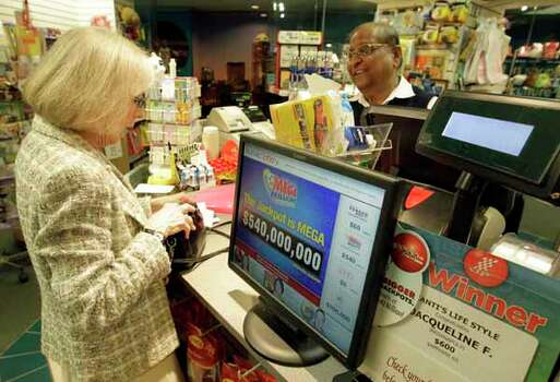 Heather McPherson buys a Mega Millions ticket from Suresh Kheradiya Thursday, March 29, 2012, in Indianapolis. It is the first time that  McPherson had bought a lotto ticket. Photo: Darron Cummings, Wire / AP