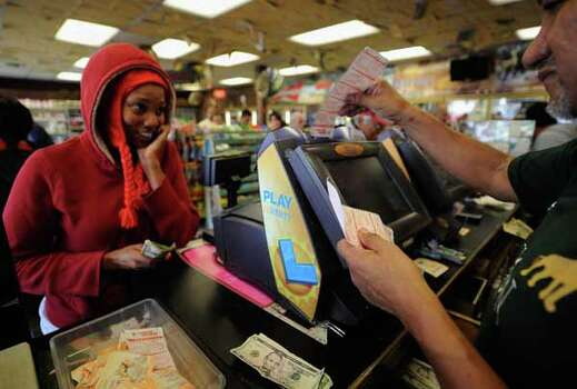 Lashawn Silver (L) looks on as Jesus Vazques helps her buy her Mega Millions tickets at Bluebird liquor store on March 29, 2012 in Hawthorne, California. The Mega Millions jackpot has reached a record high of $540 million Photo: Kevork Djansezian, Wire / 2012 Getty Images