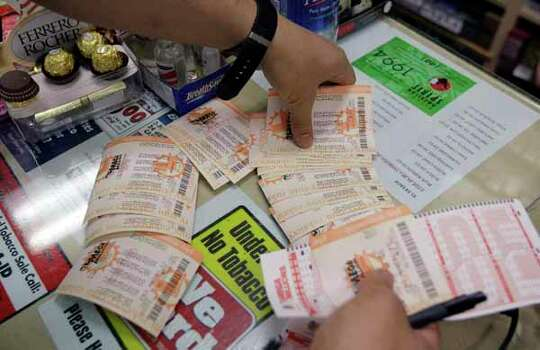 A customer collects lottery tickets that were purchased at a liquor store in Mountain View, Calif., Thursday, March 29, 2012, in hopes to win the Mega Millions lottery. The Mega Millions jackpot is now the largest in U.S. lottery history. Photo: Paul Sakuma, Wire / AP