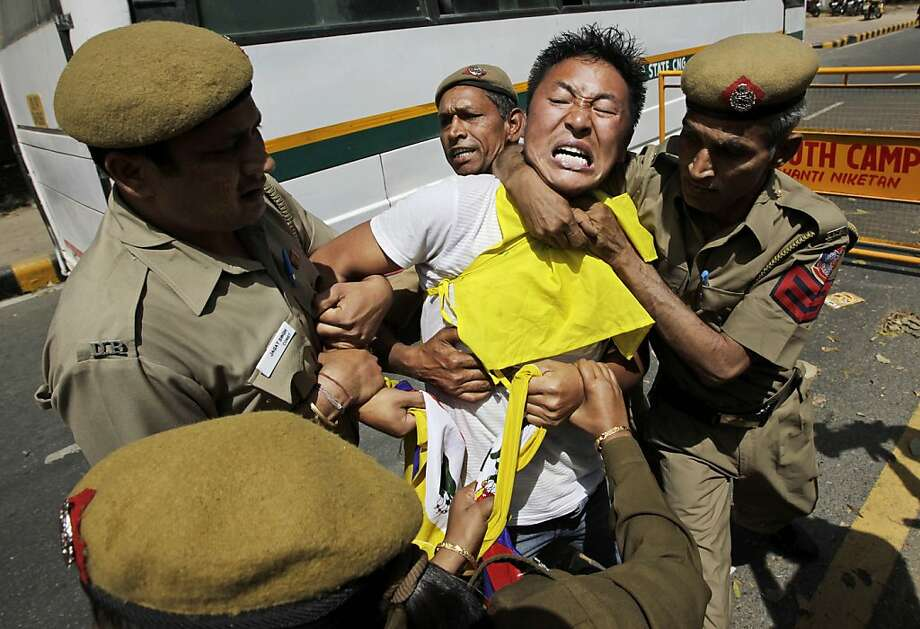 A Tibetan exile shouts slogans as he is detained by Indian police officers during a protest within a few kilometers from the venue where Chinese President Hu Jintao is attending a summit, in New Delhi, India, Thursday, March 29, 2012. Hu is in the country to attend the BRICS summit with leaders from Brazil, Russia, India and South Africa meeting. The meeting came amid heavy security following the self-immolation of a Tibetan exile at an anti-China protest Monday. (AP Photo/Manish Swarup) Photo: Manish Swarup, Associated Press