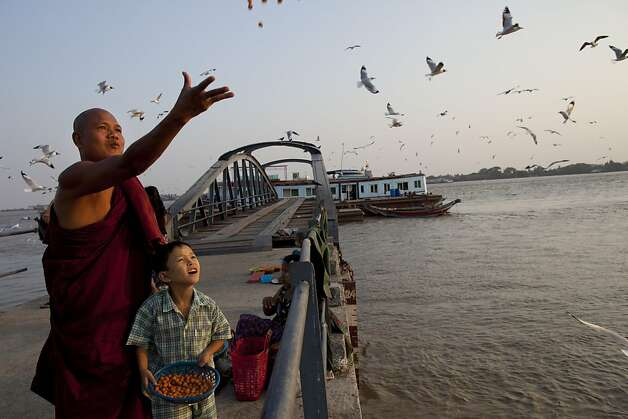 A Burmese monk and his son feed the seagulls on a jetty along the Yangon river March 29, in Yangon, Myanmar. Photo: Paula Bronstein, Getty Images