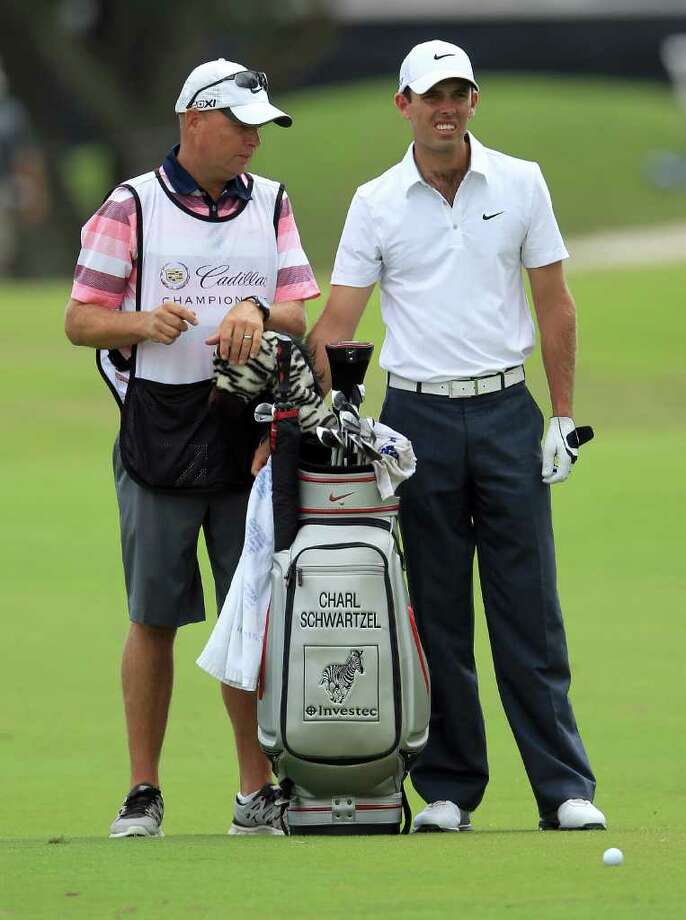MIAMI, FL - MARCH 10:  Charl Schwartzel of South Africa and caddie Greg Hearmon decide on the club before he plays his second shot at the par 5, 1st hole during the third round of the World Golf Championship Cadillac Championship on the TPC Blue Monster Course at Doral Golf Resort And Spa on March 10, 2012 in Miami, Florida.  (Photo by David Cannon/Getty Images) Photo: David Cannon / 2012 Getty Images