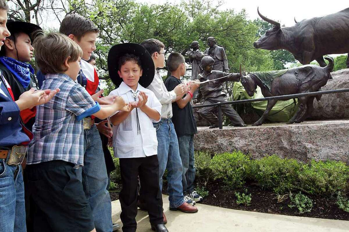 3/29/12 Ralph Barrera/American-Statesman; The ceremonial unveiling of the Tejano Monument was held on the south lawn of the Texas State Capitol with many dignitaries and special guests who were instrumental in the creation and funding of the legacy sculpture. A group of young boys gets the honor of unveiling the statue of the young boy roping a goat. (Castillo story)