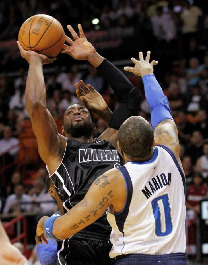 Miami's Dwyane Wade gets a shot up over Dallas' Shawn Marion. Photo: AP