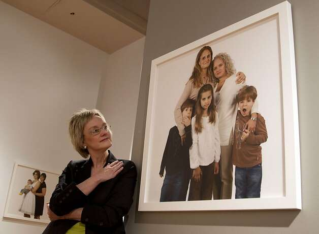 Photographer Carolyn Sherer looks at her group of photographs of lesbian families on Thursday, March 29, 2012 at the Civil Rights Institute in Birmingham, Ala.,Thursday, March 29, 2012. The photographs will be displayed  thru June. Sherer says she hopes the photographs start a conversation about equality for everyone. Photo: Dave Martin, Associated Press
