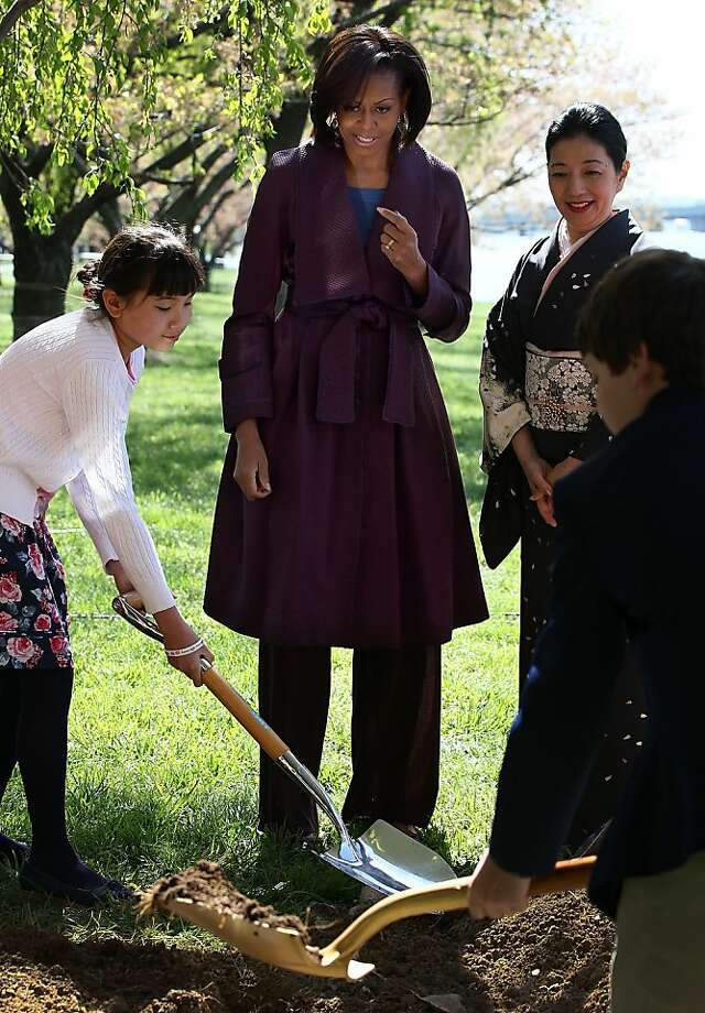 U.S. first lady Michelle Obama (C) takes part in a 1912 Cherry Blossom tree planting re-enactment ceremony with Yoriko Fujisaki (R) near the Tidal Basin and along the Potomac River March 27, 2012 in Washington, DC. 2012 marks the 100th anniversary since the United States received 3,000 Cherry Blossom trees as a gift from Japan symbolizing the friendship between the two countries. Photo: Win McNamee, Getty Images