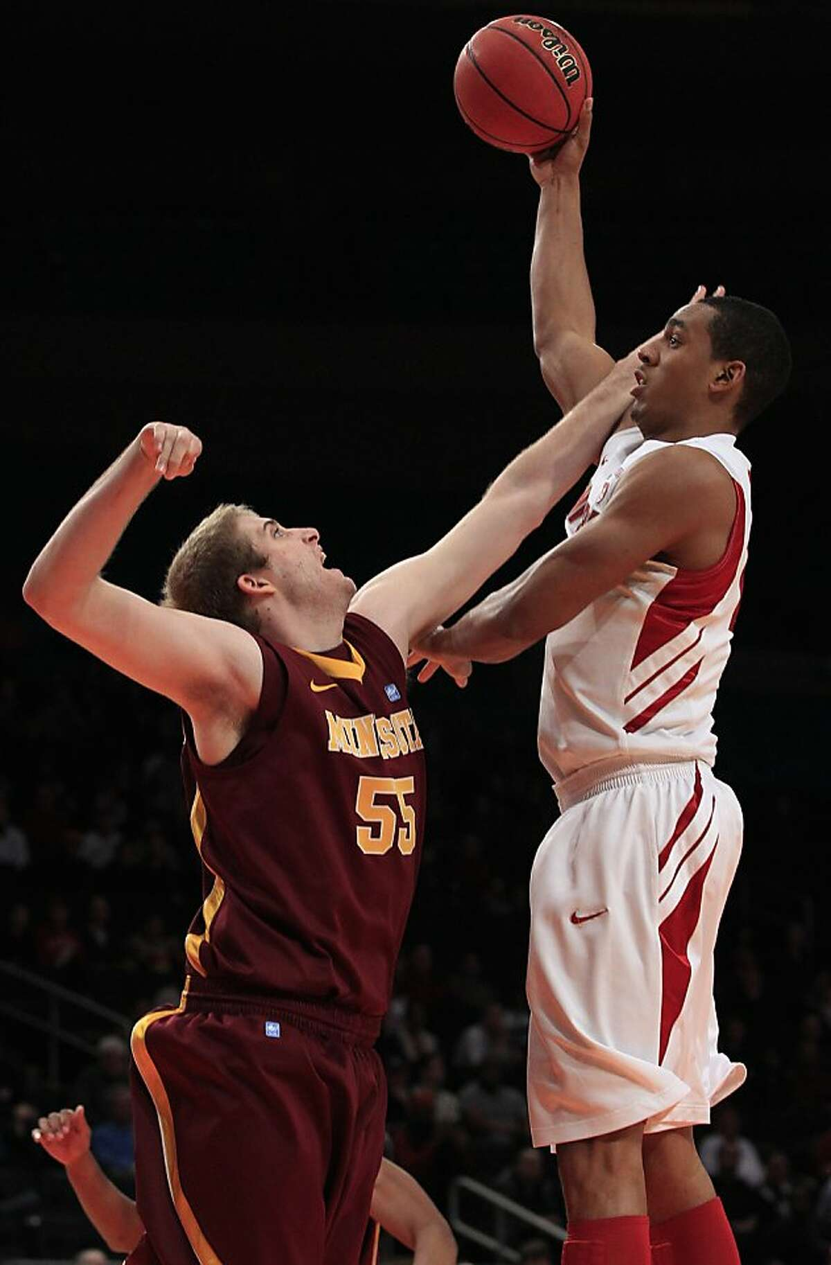 Stanford's Josh Owens, right, shoots ove Minnesota's Elliott Eliason (55) during the first half of the NIT college basketball tournament final on Thursday, March 29, 2012, in New York.