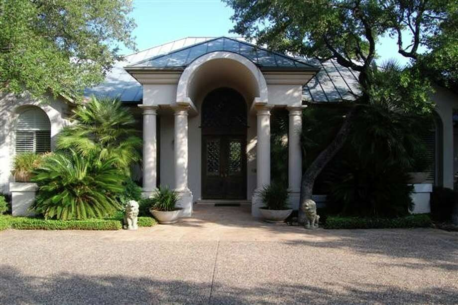 An exterior view of the front of the home, spotlighting the landscaping as well as the columns surrounding the front porch.