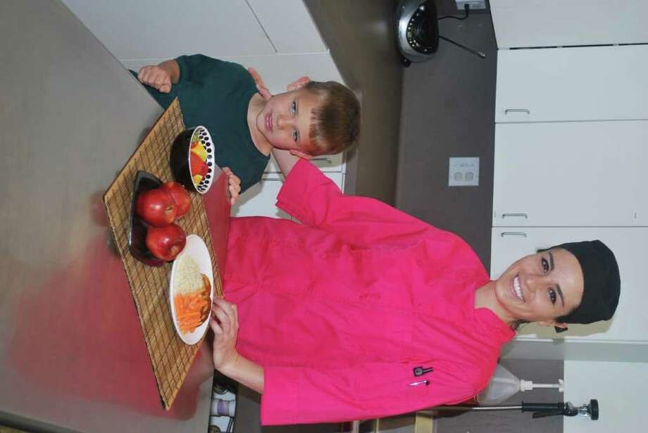 Pictured are Chef Yoli and one of the young learners at The Woodlands Young Learners Academy with a few of the new healthy menu items.