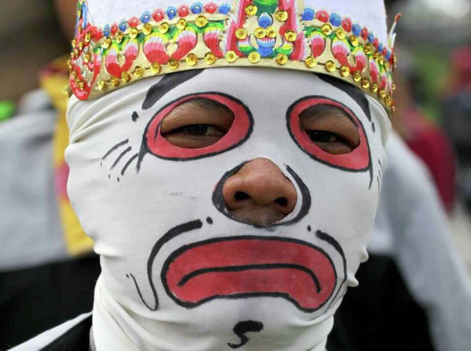 A protester wears a mask during a protest against the government's plan to raise fuel prices,  outside the parliament in Jakarta, Indonesia, Friday, March 30, 2012. The Indonesian government plans to raise fuel prices by about 33 percent next month to avoid a budget deficit due to expensive fuel subsidies. (AP Photo/Achmad Ibrahim) Photo: Achmad Ibrahim, Associated Press / AP