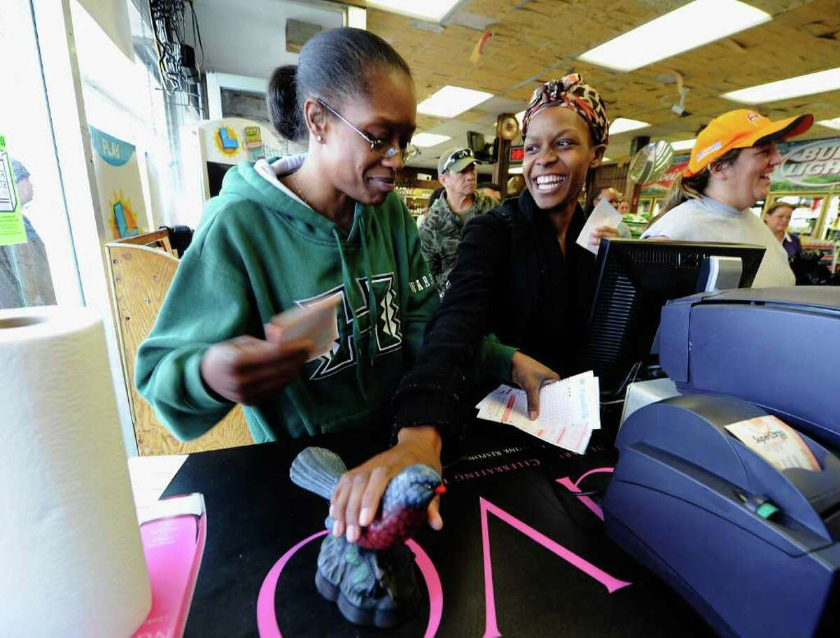HAWTHORNE, CA - MARCH 29: Jasmine Covington (R) rubs a Bluebird statuette for good luck as she looks at Keona Buckhanon after buying their lottery tickets at Bluebird liquor store on March 29, 2012 in Hawthorne, California. The Mega Millions jackpot has reached a record high of $540 million