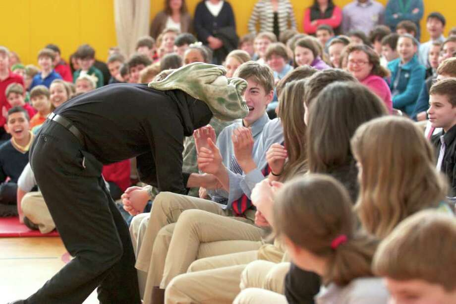"Upper School students of Eagle Hill School laugh in delight as performers from the Faustwork Mask Theater use an impressive collection of masks and astonishing physicality to portray scenes from ""Little Big Frog."" Photo: Contributed Photo"