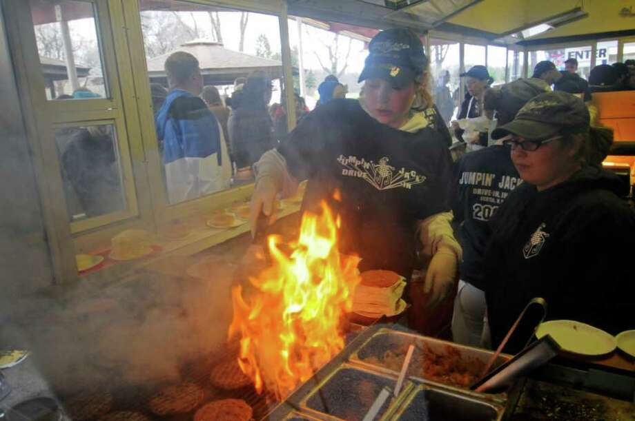 Stephanie Eddy, left, and Ashley Sherling, right,  tend the grill at Jumpin' Jack's Drive In on opening day, after the restaurant had been forced to close prematurely in 2011 after sustaining flood damage from Tropical Storm Irene, on Thursday March 29, 2012 in Scotia, NY. (Philip Kamrass / Times Union ) Photo: Philip Kamrass, Albany Times Union / 00017028A