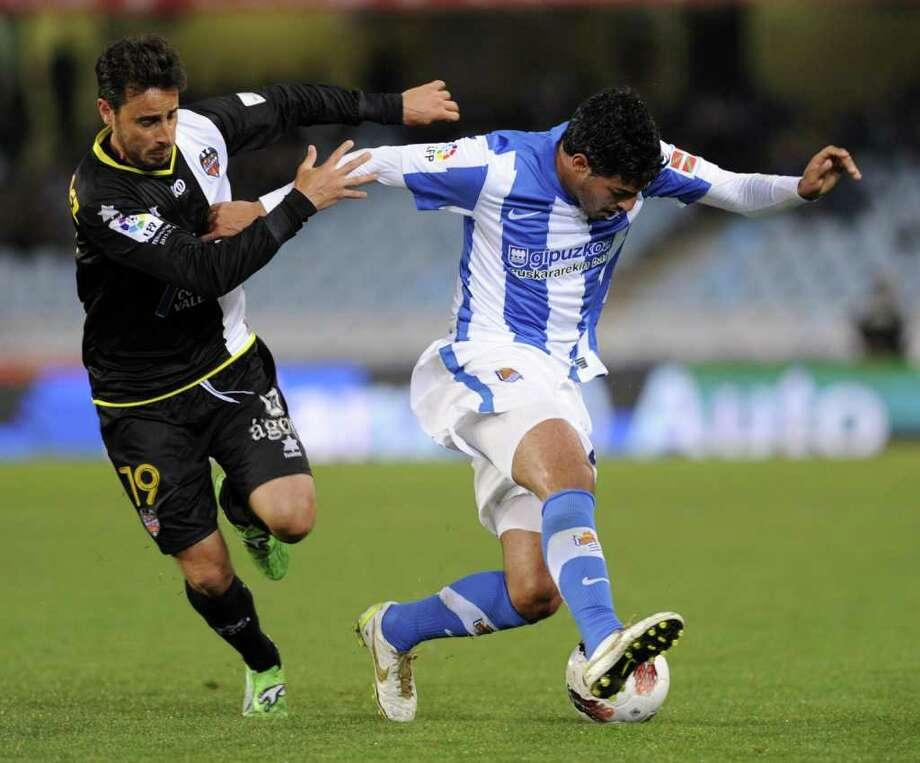 El delantero mexicano Carlos Vela (der.) controla el balón frente al defensor del Levante Pedro López (izq.) la semana pasada en el estadio de Anoeta en San Sebastián. Photo: RAFA RIVAS / AFP