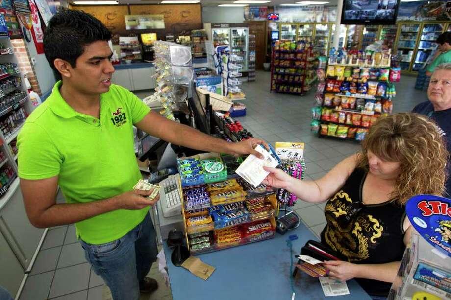 Irfan Momin, left, hands Robin Armstrong her Mega Millions tickets at Katy's Short Stop Market on Friday. Photo: Brett Coomer, Houston Chronicle / © 2012 Houston Chronicle
