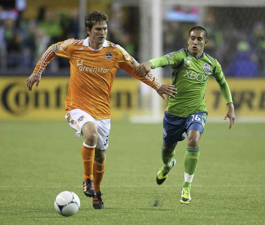 Bobby Boswell, del Dynamo, escapa de la marca del jugador de los Sounders de origen michoacano David Estrada, en Seattle. Photo: Otto Greule Jr / 2012 Getty Images