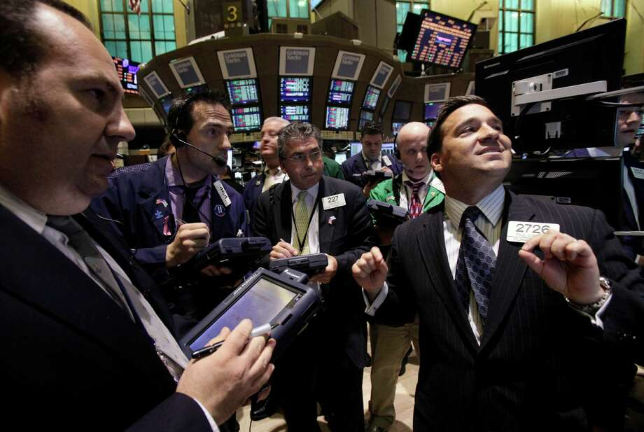 In this March 21, 2012 photo, Specialist Paul Cosentino, right, directs trading in shares of Regions Financial Corp. on the floor of the New York Stock Exchange. In the biggest jump for the start of a year since 1998, stocks closed the first three months of 2012 up 11.5 percentCK. The surprising surge has pushed the major indexes tantalizing close to their all-time highs and sent Wall Street analysts, some whose forecasts might have seemed too sunny a few months ago, scrambling to raise their estimates for the full year. Photo: Richard Drew, AP / Copyright 2012 The Associated Press. All rights reserved. This material may not be published, broadcast, rewritten or redistribu