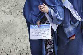 "FILE - In this Monday, March. 7, 2011 file photo, an Afghan woman holds a pamphlet saying ""according the 22nd article of the national constitution, any kind of discrimination between Afghans is forbidden, all Afghan men and woman have equal rights""  during a march with Women for Women International at Kabul University in Kabul, Afghanistan.  Afghanistan's criminal justice system has made little progress in the way it treats women accused of running away or adultery, despite public commitments from the Afghan president to protect women's rights, Human Right Watch said. (AP Photo/Hossein Fatemi, File)"