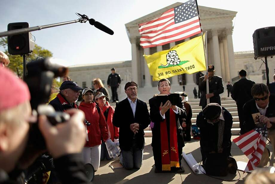 WASHINGTON, DC - MARCH 28:  Rev. Rob Schneck (C) leads people in prayer outside the U.S. Supreme Court on the third day of oral arguements over the constitutionality of the Patient Protection and Affordable Care Act March 28, 2012 in Washington, DC. Today is the last of three days the high court set to hear arguments over the act.  (Photo by Chip Somodevilla/Getty Images) Photo: Chip Somodevilla, Getty Images