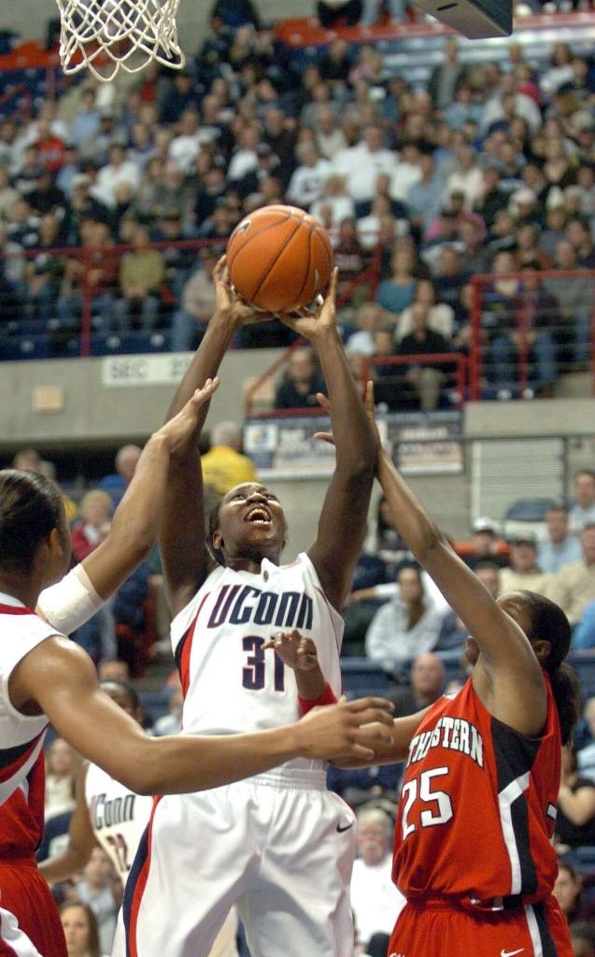 UConn's Tina Charles puts up the ball as Northeastern's Kashaia Cannon defends during the first half of Saturday's season opener at Gampel Pavilion