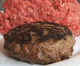 "A hamburger made from ground beef containing what is derisively referred to as ""pink slime,"" or what the meat industry calls ""lean, finely textured beef,"" is ready for tasting Thursday, March 15, 2012 in Concord, N.H.  Under a change announced Thursday by the U.S. Department of Agriculture, districts that get food through the government's school lunch program will be allowed to say no to ground beef containing the ammonia-treated filler and choose filler-free meat instead. The low-cost filler is made from fatty meat scraps that are heated to remove most of the fat, then treated with ammonium hydroxide gas to kill bacteria such as E. coli and salmonella. (AP Photo/Jim Cole)"