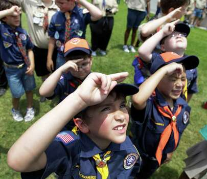 A group of Cub Scouts from Pack 355 salutes as an American flag is raised at the Houston National Cemetery in a Memorial Day ceremony in May 2011. Below, space shuttle astronaut Michael Fossum, an Eagle Scout, answers questions at a news conference at the Kennedy Space Center. Photo: Melissa Phillip / © 2010 Houston Chronicle