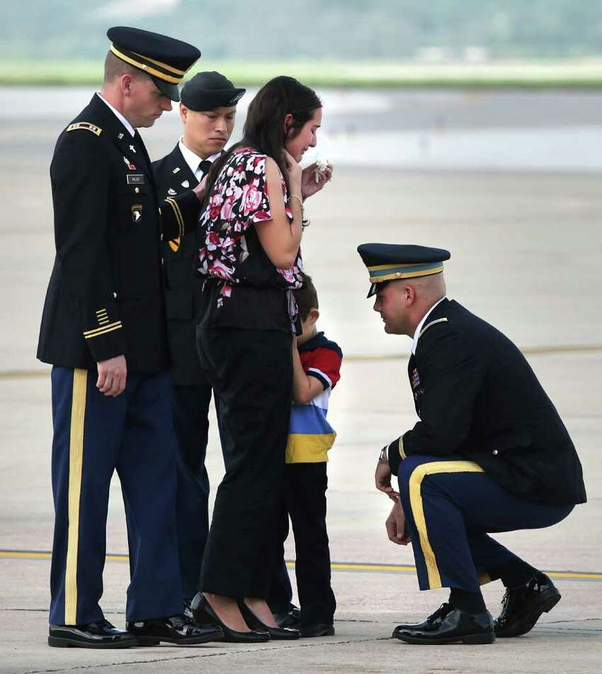 An unidentified U.S. Army officer, right, consoles Dean Ray, 5, hiding behind his mother Shannon Ray's leg, after the remains of Army 1st Lt. Clovis T. Ray, Dean's father, arrived at the Kelly Field Flightline. Ray died March 15th in the Kunar province in Afghanistan. Friday, March 30, 2012. The memorial service for Ray is Saturday at the Live Oak County Coliseum between Three Rivers and George West. Three Rivers Mayor James Liska recalls Army Lt. Clovis Ray as a leader even when they both played on a high school football team that made the state playoffs two years in a row.