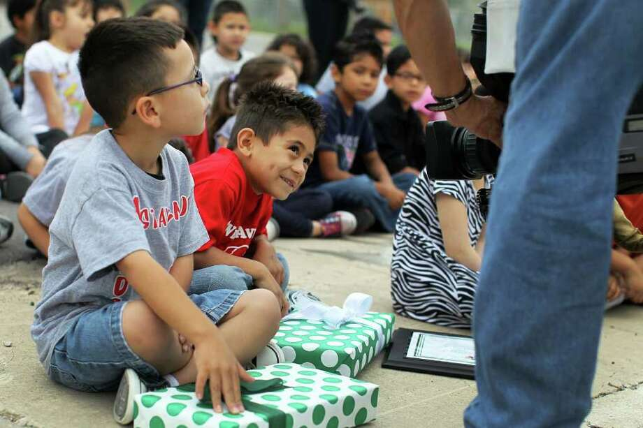 Kindergartener Jasiah Rubalcava (center) smiles for a television camera during a ceremony where he was recognized by Acadian Ambulance Service for his recent act of heroism after he gave his friend Nicholas Carvajal (left) the Heimlich when he noticed his friend choking on a bite of food during lunch at West Avenue Elementary School, Friday, March 30, 2012. Photo: JENNIFER WHITNEY, Jennifer Whitney/ Special To The Express-News / special to the Express-News