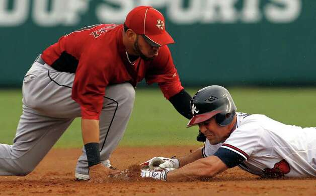 Atlanta's Jack Wilson (right) slides safely under the tag of Houston shortstop Marwin Gonzalez for a double in the first inning during Friday. Photo: AP