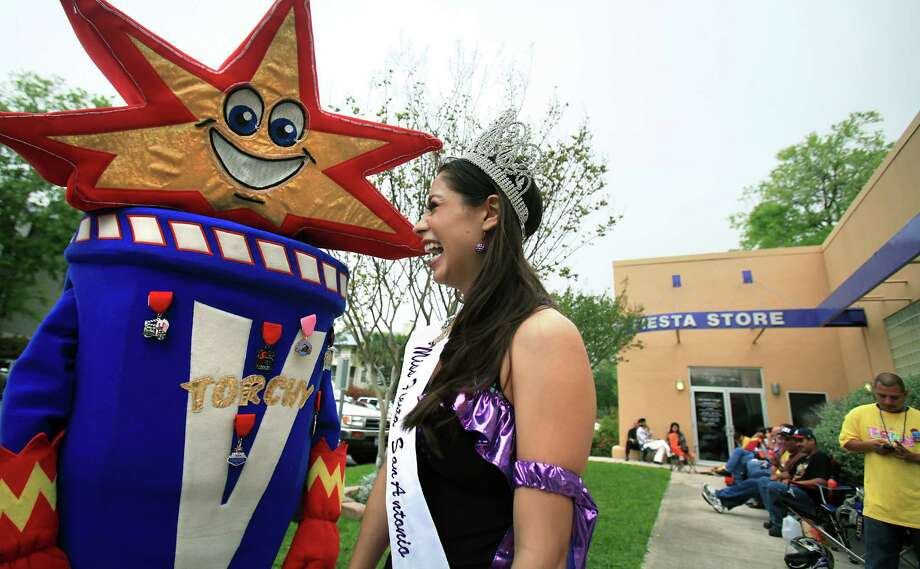 """Katie Rivera Miss Fiesta SA 2012, right, enjoys a laugh with Fiesta Flambeau Association mascot """"Torchy"""" as Fiesta fans sit in line at The Fiesta Store on Broadway waiting for the store to open to get tickets to Fiesta events. Friday, March 30, 2012. Bob Owen/San Antonio Express-News. Photo: BOB OWEN, San Antonio Express-News / © 2012 San Antonio Express-News"""