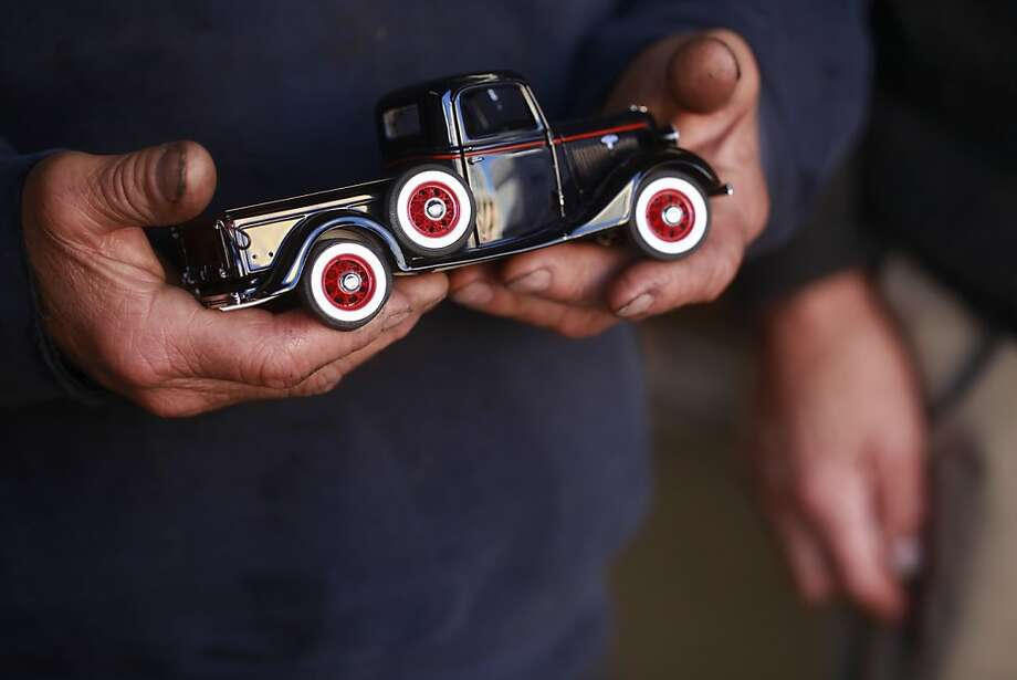 Owner of Allied Engine & Auto Repair, Paul Grech holds a model of his black 1936 Ford pickup in San Francisco, Calif. Photo: Mike Kepka