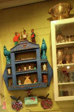 Folk art in a blue altar over the kitchen sink; the colorful glasses in the cabinet to the right of the sink were made by WardÕs son Dakota, a glassblower. Photo: DANNY WARNER