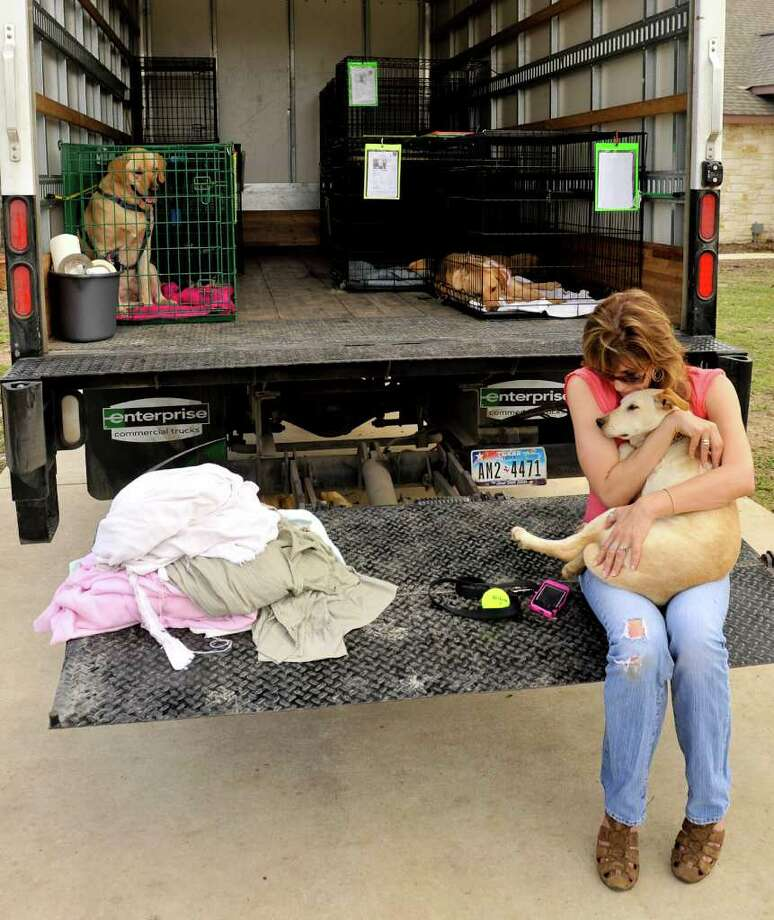 Tracy Voss hug's one of the dog's that her project, Tracy's Dog's, has found a home for. This dog was part of a truckload going to Colorado to new homes. Photo: Robin Jerstad/For The Express-News