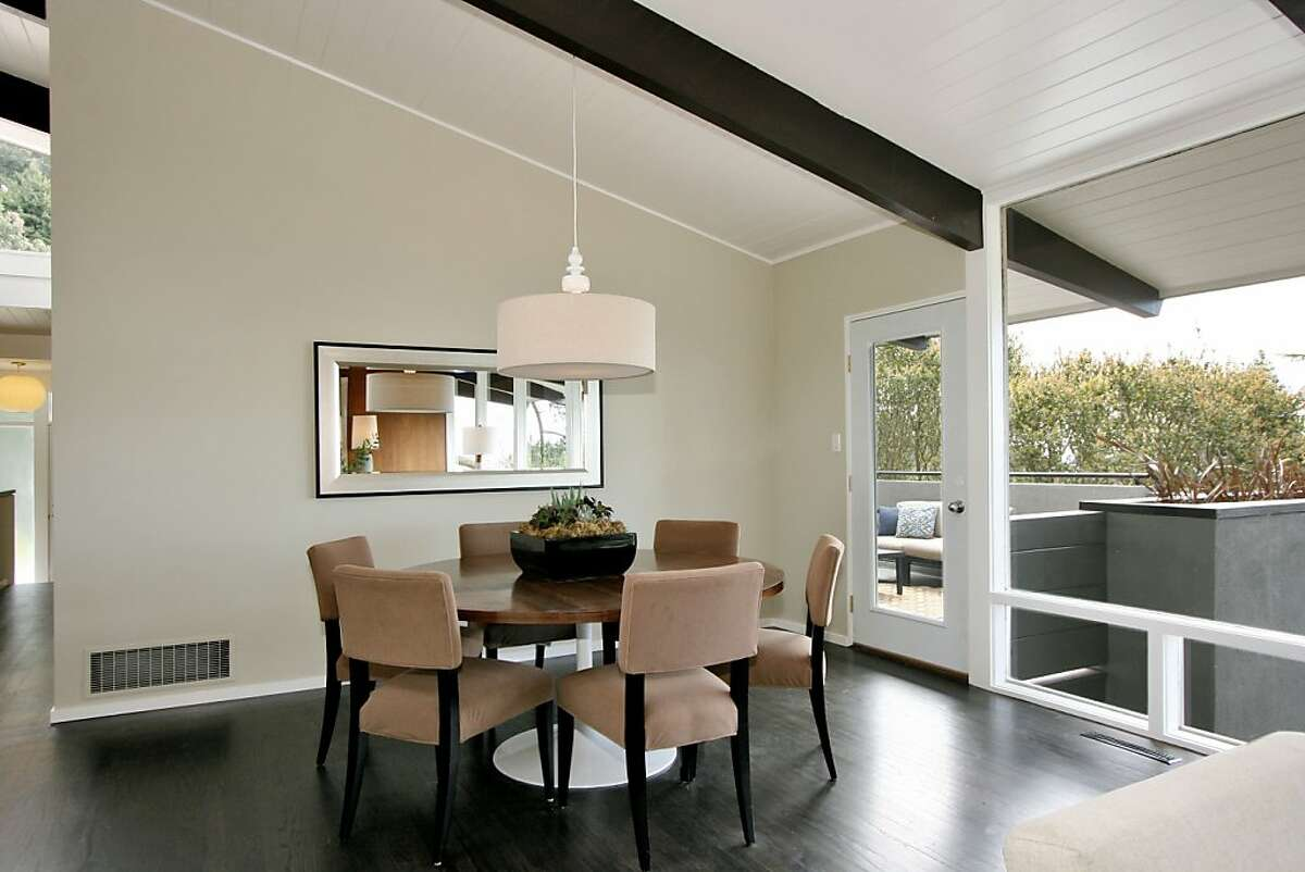 A vaulted ceiling, wall of windows and hardwood floors are features of the contemporary dining area.