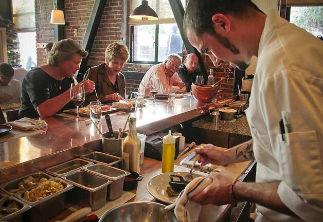 Daniel Maragoudakis prepares a dish in front of diners at Cotogna, which blends California and Italian styles in a casual setting overlooking Jackson Square in S.F. The nightly three-course menu is a deal. Photo: John Storey, Special To The Chronicle