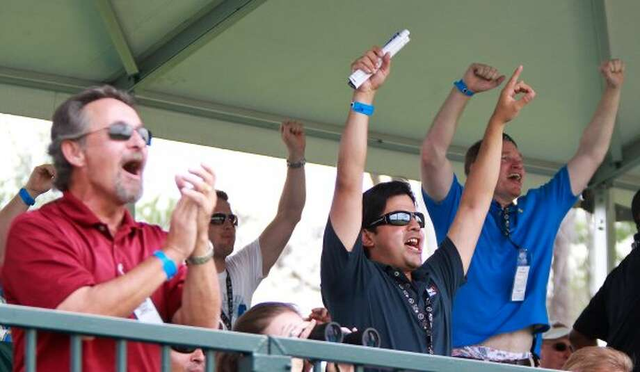 Francisco Diaz, of Houston, and the rest of the the rowdy fans of the 16th hole gallery cheer for their favorite caddy to race to the green. (Nick de la Torre / Houston Chronicle)