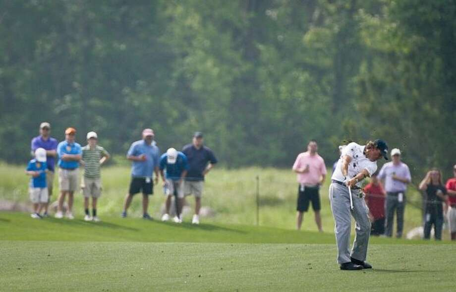 Phil Mickelson tries an approach shot at the 18th hole to finish the first round. (Nick de la Torre / Houston Chronicle)