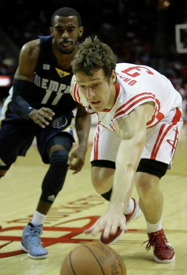 The Houston Rockets Goran Dragic reaches for loose ball ahead of Memphis Grizzlies Mike Conley during first half of NBA game at Toyota Center Friday, March 30, 2012, in Houston. Photo: Melissa Phillip, Houston Chronicle / © 2012 Houston Chronicle